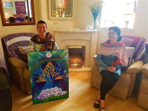 Micina gifting a painting to Cork Cancer Care Centre.