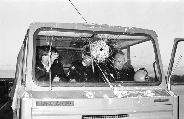 Gardaí in a truck damaged by rioters.