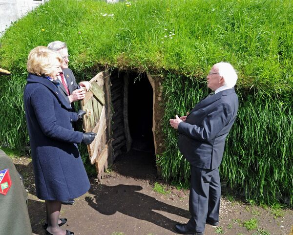 President Michael D. Higgins, Sabina Higgins and Prof. Patrick O'Shea, President, UCC, speaking as they visited An Bothán, a mud cabin, re-created by UCC staff, at the National Famine Commemoration at UCC. Picture: Denis Minihane.