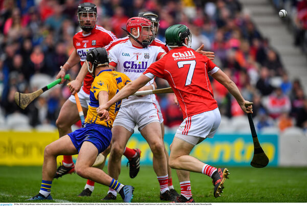 Anthony Nash clears under pressure from team-mate Mark Coleman and David Reidy of Clare. Picture: Brendan Moran/Sportsfile
