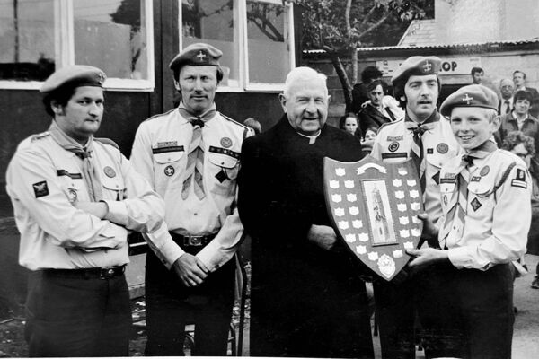 The Dean of Cork, Rt Rev. Mgr J. Bastible, P.P., V.G., on his first visit to Kilcully Camp in May 1981 presents the Cork North Area Shielda to Patrol M.O'Callghan of the 12th Cork (St. Patrick's) Troop. Also in the picture are from left Jim O'Driscoll, Area Commissioner, Michael Milner and Ray Lougheed, leaders of the troop. Pic: D.P.Barry