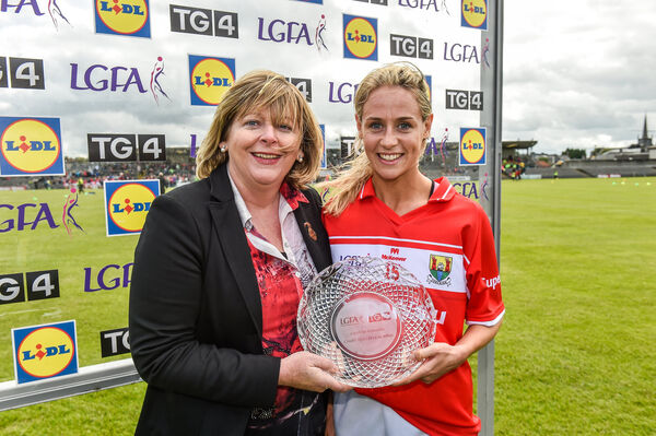 Orla Finn is presented with her player of the match award by LGFA President Marie Hickey. Picture: Matt Browne/Sportsfile