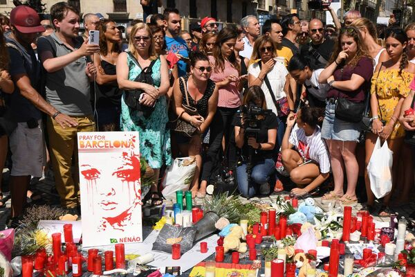 People stand next to flowers, candles, a poster reading 'Pray for Barcelona' and other items set up on the Las Ramblas boulevard in Barcelona as they pay tribute to the victims of the Barcelona attack. Pic: Pascal Guyot/AFP/Getty Images