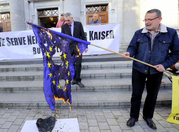 Cork County Councillor Diarmuid O'Cadhla burning the EU flag in protest outside the Cork City Hall during an anti-EU rally on Europe Day. Pic: Gavin Browne