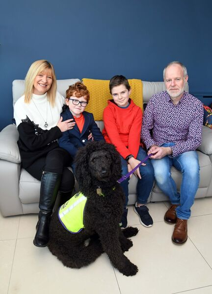 Terry O'Connor and Marisa Geary and their sons Ríain and Louie at home with Maisie the standard poodle from Dogs for the Disabled.
