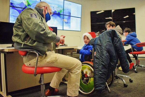 NSC CEO Rory FitzPatrick explains maritime satellite observation to Adam King (6) while brothers Danny (13) and Robert (8) look on. Picture: Zoe FitzPatrick.