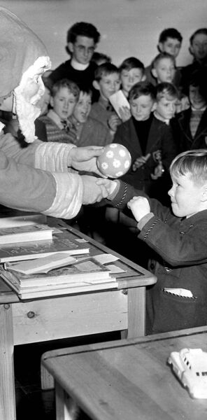 Santa — wearing a mask that looks scary to modern eyes! — hands out Christmas presents to young students at Presentation Brothers College, Cork, on December 22, 1956