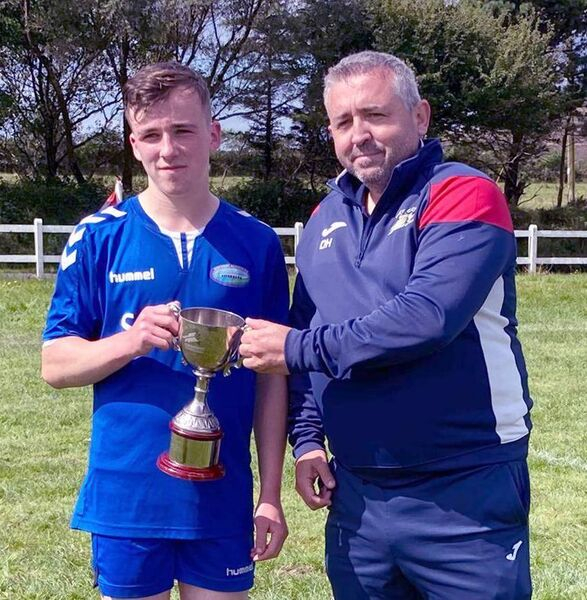 Riverside Athletic captain William Hennigan accepting the 2020 SuperValu West Cork Schoolboys League U16 Cup trophy from WCSL Committee member David Hall.