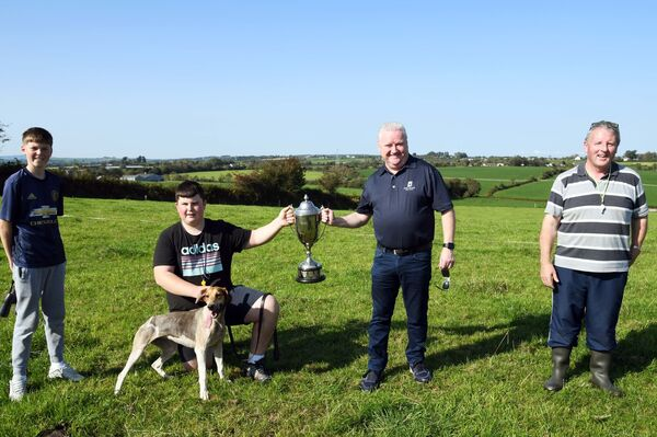 Tomás Singleton, Singleton SuperValu, presenting the trophy to John and Seán O'Sullivan, Griffin United, winners of the Cork City & County Harriers Association All-Ireland Puppy Draghunt near Blarney with Melody. Left is John's nephew Callum Wolfe. Picture Denis Minihane