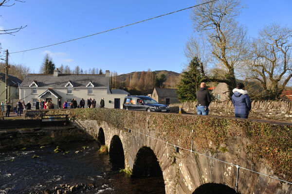 The hearse passes over the River Sullane at Ballingeary as mourners make their way from the church. Picture: Larry Cummins
