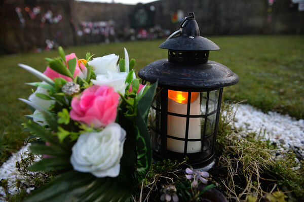 A candle is lit at the Tuam Mother and Baby burial site in Tuam. Picture: Ray Ryan