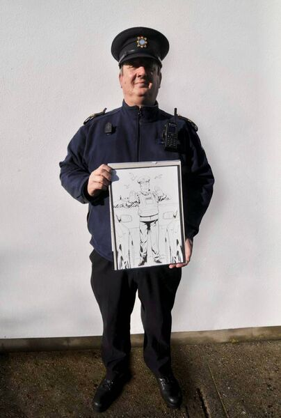 Garda Mick O'Brien with the artwork commissioned of him.