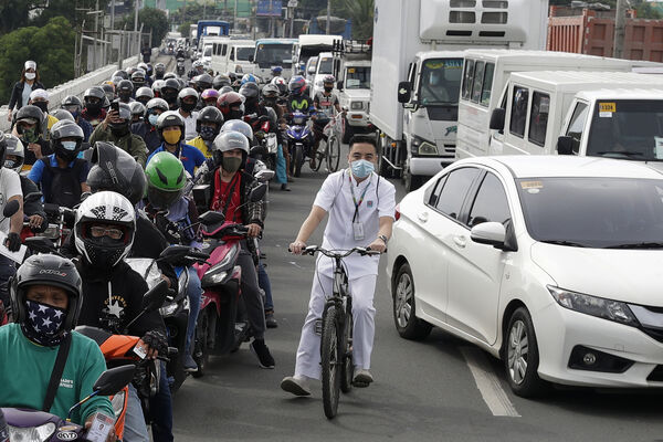 A man rides his bicycle as traffic creeps though a checkpoint outside Manila, Philippines, during one of the country's lockdowns to curb the surge in coronavirus cases. (AP Photo/Aaron Favila)