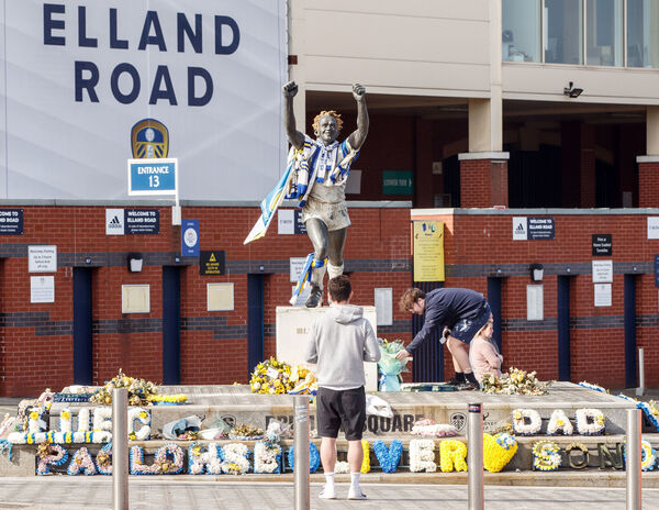 A man lays a floral tribute outside Elland Road in Leeds.