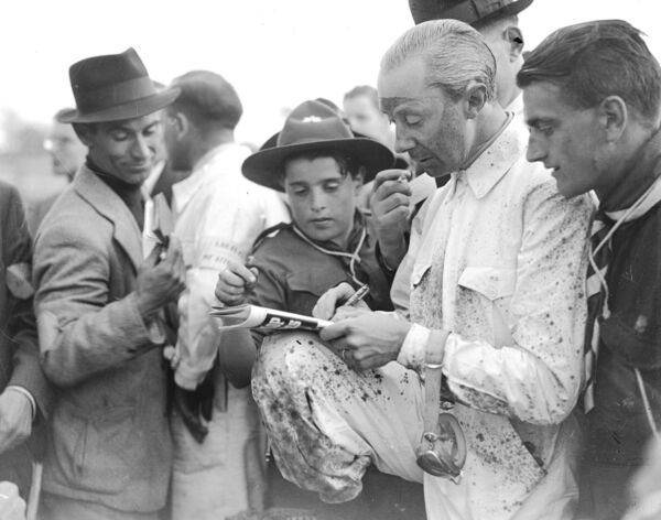 René Dreyfus signing autographs for a boy scout after his win in the Grand Prix.