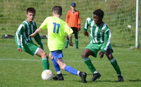 Ryan Hackett of Leeds attempts to weave past Ryan Dalton and Golding Nduwuba of Passage during the CSL U14 Division 1 match at Maulbawn. Picture: Howard Crowdy